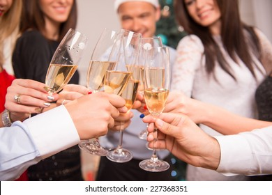 Selective focus on the glasses of champagne in the hands of friends celebrating the New Year on background