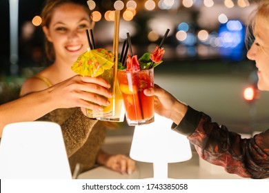 Selective focus on the glasses of three young women making a toast with cocktails on a terrace at night with the city lights on the background