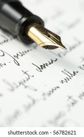 Selective focus on gold pen over hand written letter. Focus on tip of pen nib.