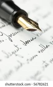 Selective focus on gold pen over hand written letter. Focus on tip of pen nib.