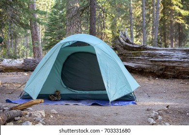 Selective focus on green tent in campground among pine trees at Lassen Volcanic National Park, California, USA, with a pair of sandals on the outside.