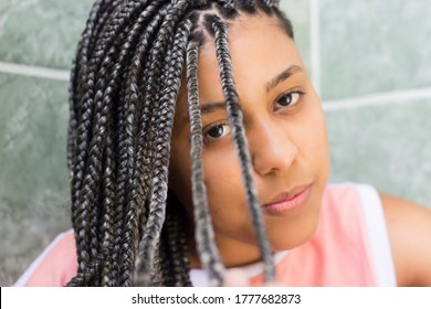 Selective focus on hair. Portrait of a young afro woman with box braids