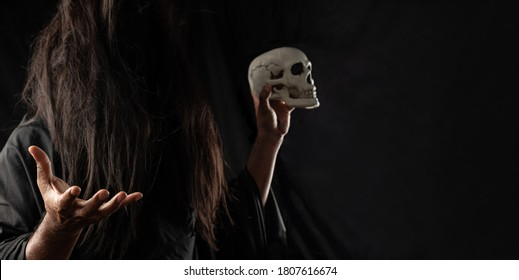Selective Focus on Hand of Wizard or Witch, Sorcerer with Skull Ghost Halloween On Dark Black Background with Copy Space. Horror, Scary, Spooky, Haunted, Creepy, Ghostly, Background Concept.
