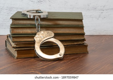 selective focus on handcuffs and a stack of books on a wood table for the concept of literary freedom