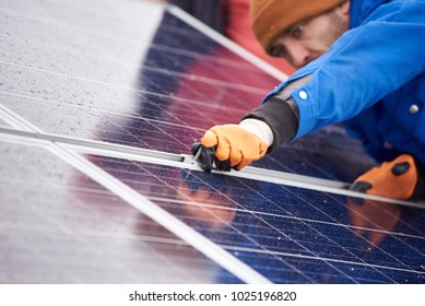 Selective focus on the hands of a professional male electrician installing solar panels working on alternative energy sources farm clean green environment friendly energy modern technology.