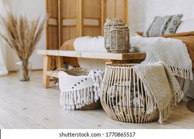 Selektiver Fokus auf die Inneneinrichtung. Komfortables Schlafzimmer im böhmischen Stil mit Stoffbeet auf dem Bett, Sitzbank aus Holz, Bambusverkleidung, trockene Pflanzen in Vase, Korbkorb