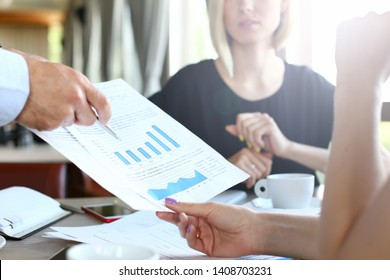 Selective focus on important paper with biz information. Thoughtful group of company colleagues discussing important corporate charts and graphs indoors. Man and women sitting in cafe.