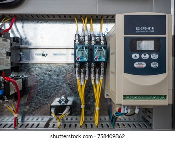 The selective focus on an inverter to control the rpm of motor which is the heart of machine in an industry. Besides are fuse and magnetic wiring along the busbar behind.