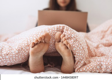 Selective focus on the legs. Young adult beautiful girl enjoys a laptop in bed. She works either on the Internet or watching a movie.