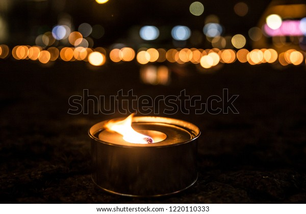 Selective focus on a lit outdoor candle(also known as pitch torch or a garden candle), a lot of out of focus candles burning on the background at night.