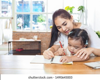 Selective Focus on little girl. Adorable girl concentrate on writing practice trained by her mother at home. Mom and little girl educate together.