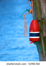 Selective focus on Lobster Buoy. Lobster Buoy tied with rope to a wood pier pylon.  Blue rough ocean water background