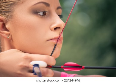 Selective focus on the lovely young fair-haired woman pulling the bowstring