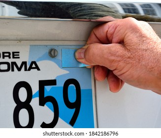 Selective focus on a male thumb aligning and applying a blank blue registration sticker with copy space as a required tag for an annual license plate renew on rear license plate.