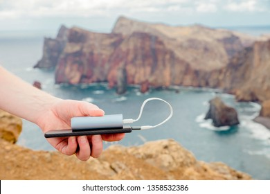 Selective focus on man holding a black smartphone and portable power bank and charging phone, overcast cloudy sky day. Travel and technology concept.