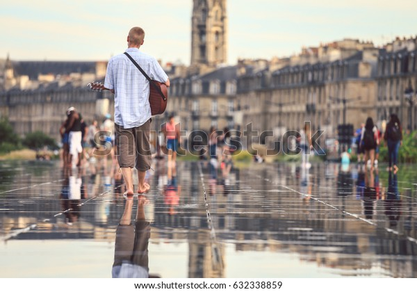 Selective focus on a man holding guitar at Bordeaux water mirror full of people in one of the hotest summer day, having fun in the water