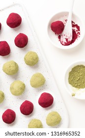 Selective focus on matcha green tea and pink raspberry beetroot truffles close up, white background, copy space - gourmet healthy dessert, top view