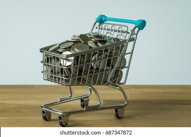 Selective focus on mini shopping cart with full of coins as shopping concept.