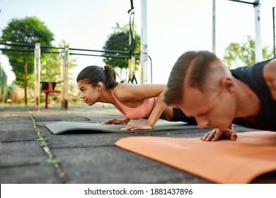 Selective focus on mixed race young girl training oudoors with young caucasian man pushing up on mats, widescreen. Healthy lifestyle and street sport concept