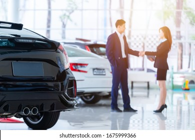 Selective focus on a new car and blur the dealership professional salesman and his client shaking hands. concept professionalism agreement contract leasing renting retail car sales .