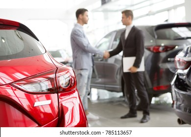 Selective focus on a new car at the dealership professional salesman and his client shaking hands on the background copyspace professionalism agreement contract leasing renting retail sales.
