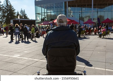 Selective focus on old man form the back sitting at open public space. People gathered for climate change protest and conference at background.