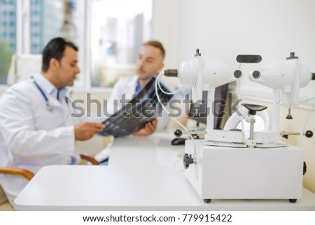 61de7d3674c Selective focus on ophtalmic machine at the clinic copyspace two male  doctors talking on the background professionalism ophtalmology eye  examination checkup ...