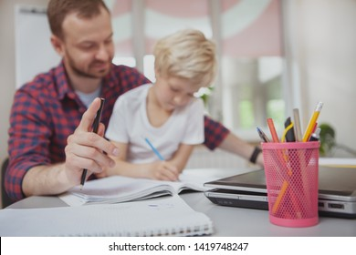Selective focus on pens and pencils on foreground, little girl and her teacher drawing together on background, copy space. Art class teacher helping his cute little student