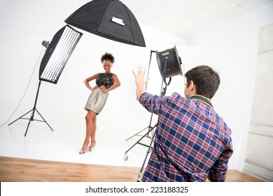 Selective focus on the photographer wearing nice checked shirt standing back to us animated his work photographing the model on background