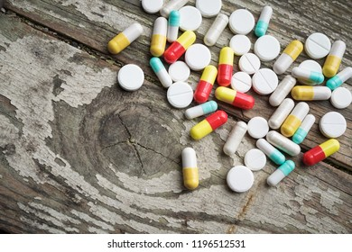 Selective focus on pill spread on wooden background. Global healthcare concept. Pharmaceutical industry. Drugs in medical container on wooden background.