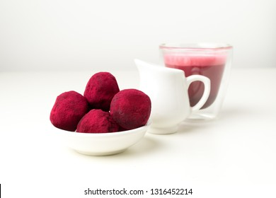 Selective focus on pink raspberry beetroot truffles close up, white background, copy space - gourmet dessert