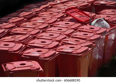 Selective focus on red color recycling bins in a group.