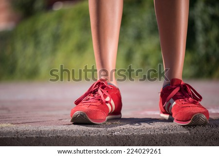 Selective focus on red jogging shoes of woman standing on the stairs