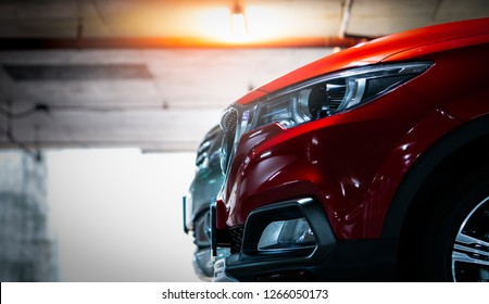 Selective focus on red shiny SUV sport car parked at shopping mall indoor parking lot. Headlamp lights with elegant and luxury design. Automotive industry and hybrid car concept. Underground parking.
