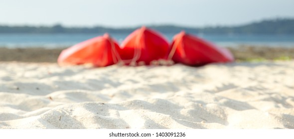 Selective focus on sand, cannoe stand on a sandy beach.  Red kayaks on the tropical beach, Active rest, sport. Summer concept