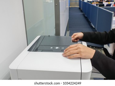 selective focus on secretary with black suit uses office printer for copying and scanning the important documents