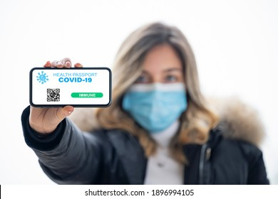 (Selective focus, focus on the smart phone) A defocused young girl, wearing a face mask, is holding a smart phone with a digital illustration of a Covid-19 Health Passport concept.