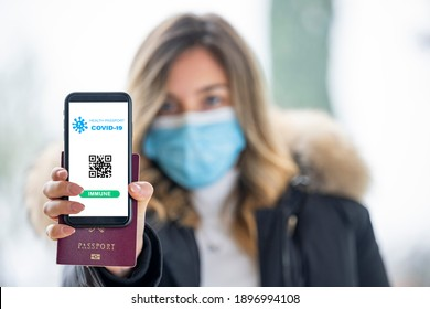 (Selective focus, focus on the smart phone) A defocused young girl, wearing a face mask, is holding a passport and a smart phone with a digital illustration of a Covid-19 Health Passport concept.