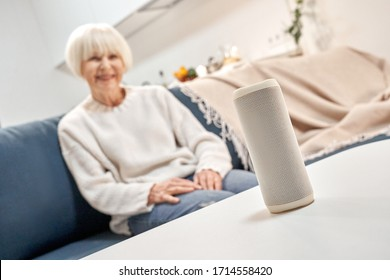Selective focus on smart speaker and wireless digital assistant against happy retirement woman sitting on couch in living room, spending weekend at home