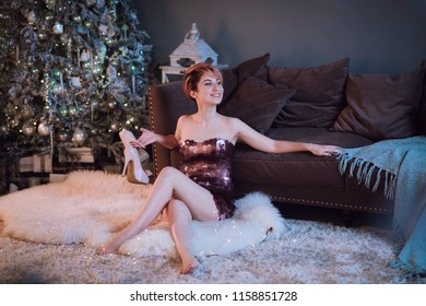 Selective focus on the smiling beautiful woman wearing nice evening dress  Christmas tree, presents and gift boxes under it. New Year decorations.