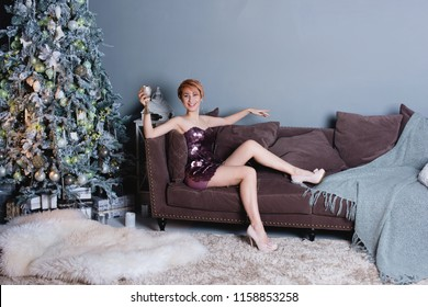 Selective focus on the smiling beautiful woman wearing nice evening dress holding a glass congratulating us with the New Year. Christmas tree, presents and gift boxes under it. New Year decorations.