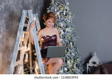 Selective focus on the smiling beautiful woman wearing nice evening dress holding a notebook and congratulating us with the New Year. Christmas tree, presents and gift boxes under it. New Year decorat