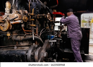 Selective focus on steam engine elements or parts in steam train cabin with blurred engineer or train driver working on cranks, Ireland