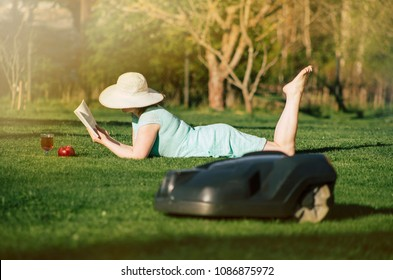 Selective focus on summery woman who lays on the grass and reads the book, enjoys not having to have to mown the lawn itself as an robotic lawn mower mows the lawn concept.