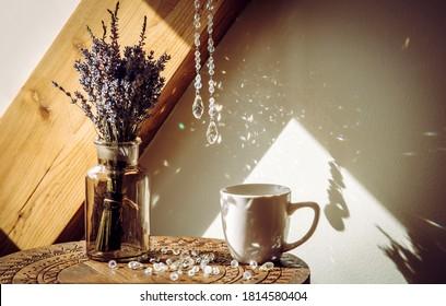 Selective focus on tear drop shape crystal rainbow maker suncatcher hanging in home. Good Feng Shui, Sha Chi reflection.