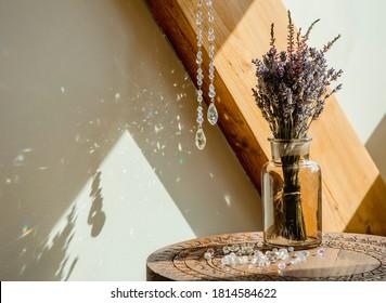 Selective focus on tear drop shape crystal rainbow maker suncatcher hanging in home. Good Feng Shui, Sha Chi reflection, energy flow concept.