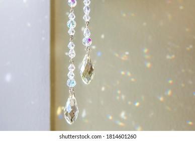 Selective focus on tear drop shape crystal rainbow maker suncatcher hanging in home. Good Feng Shui, Sha Chi energy flow concept.