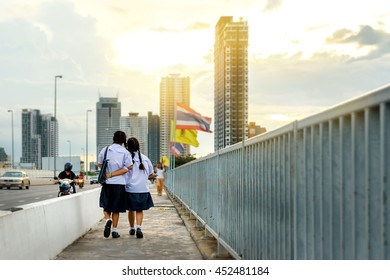 Selective focus on two schoolgirls , Flare light effect , Two asia schoolgirl walk across the bridge back home in the afternoon , Back view