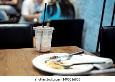 Selective focus on used plastic glass on the wooden table with blurred dirty dish in foreground and defocused customers in background