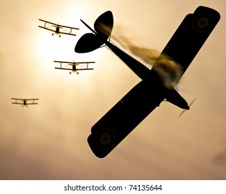 Selective focus on vintage plane of fire.  Three world war one double wing biplanes coming out of the sun to shoot down enemy plane.  Original Illustration